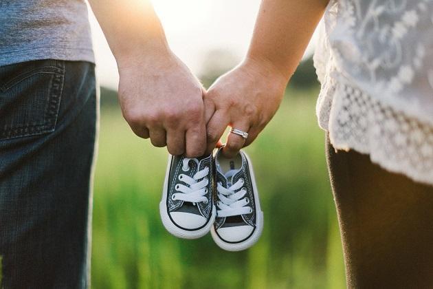 Мужчина и женщина несут детские тапочки