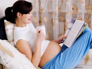 Беременная девушка пьет кофе