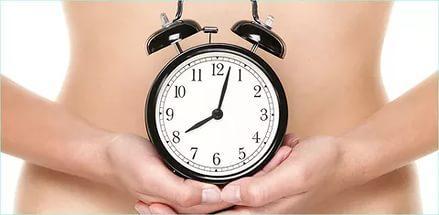 Часы на фоне живота