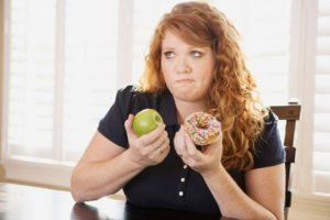 Полная девушка выбирает между пончиком и яблоком