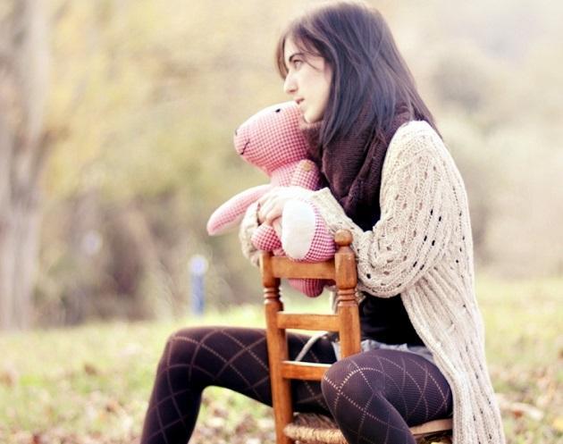 Грустная девушка с детской игрушкой