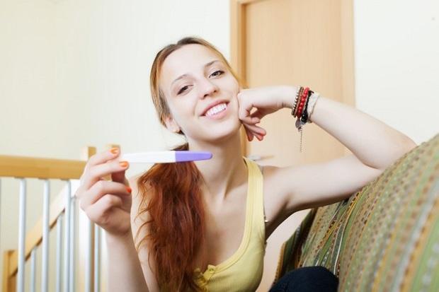 довольная девушка с тестом на беременность